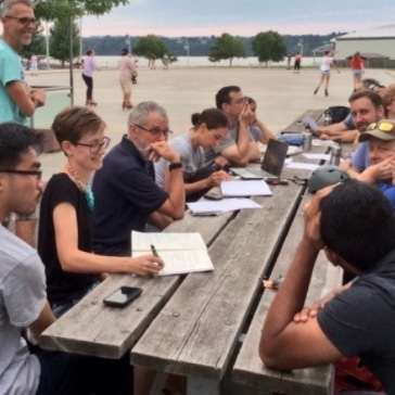 A group of about 10 people sitting around a picnic table outside having a discussion