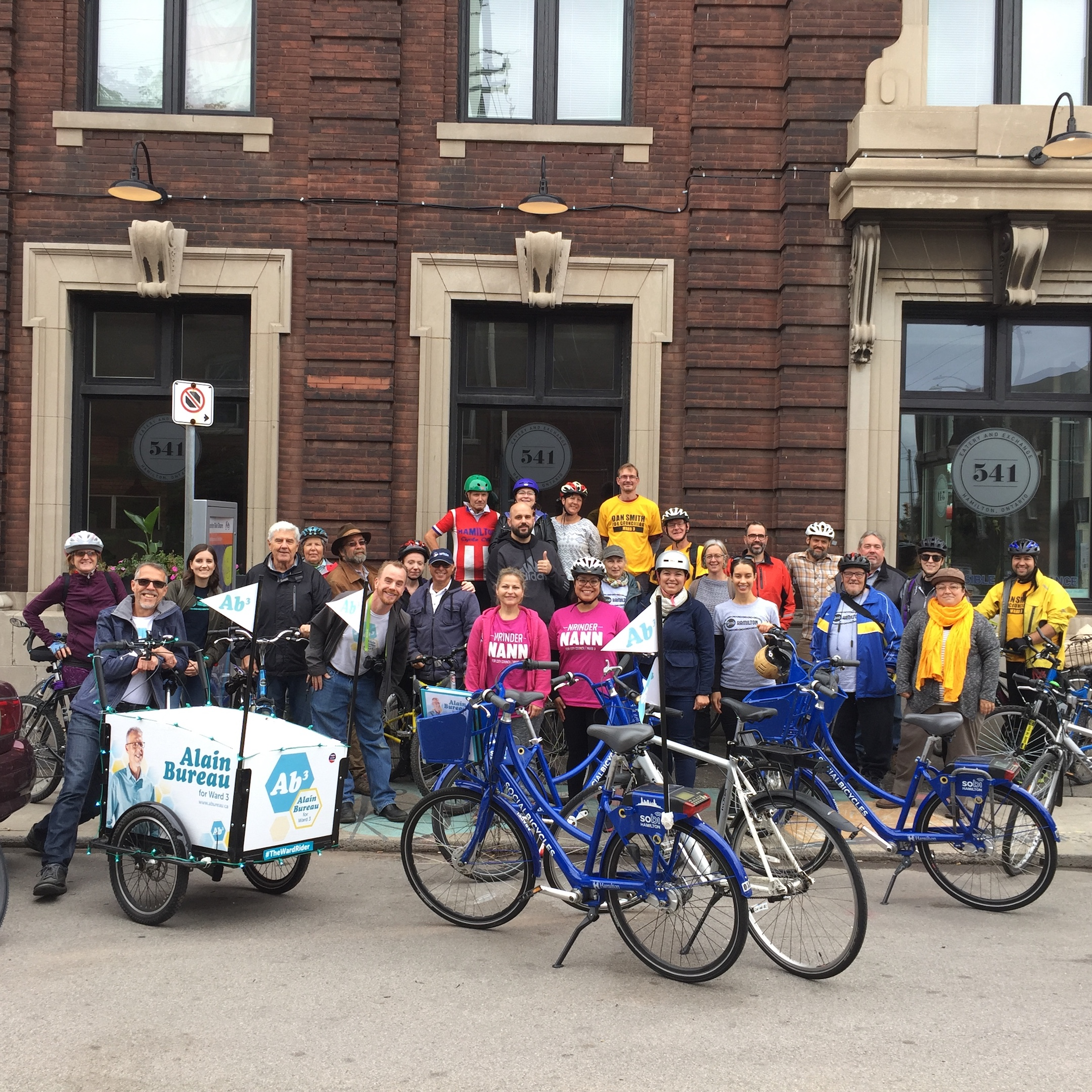 A large group of about 30 people standing in front of a coffee shop with bicycles before heading out on a bike ride