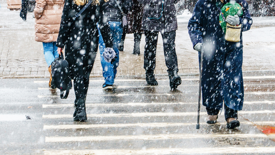 People walking through a crosswalk in the snow, visible from the waist down