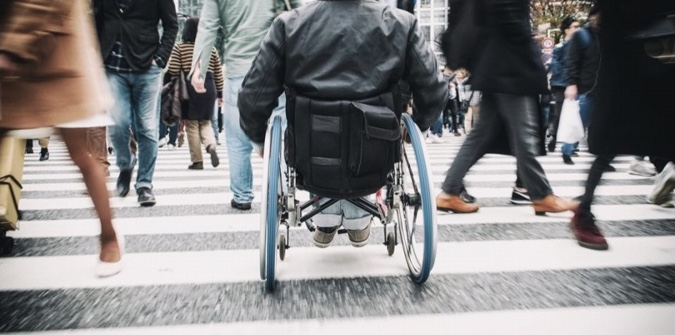 Busy crosswalk with people walking and a person in a wheelchair in the centre