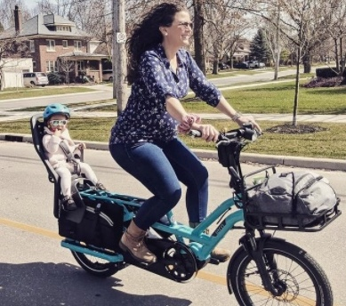 Photo of a woman who is pregnant riding a bright blue electric bicycle with a toddler in a child seat riding on the back