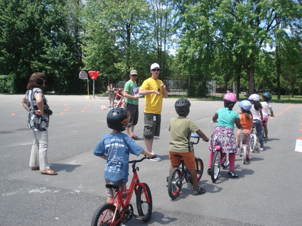 A group of elementary school children lined up on bicycles learning to ride bikes