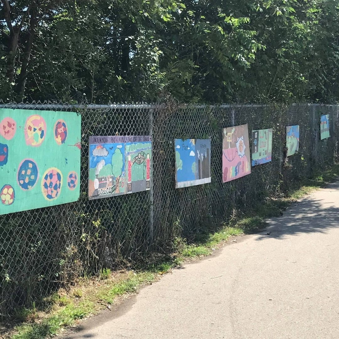 Children's art hung on a fence in a park along a multi-use path