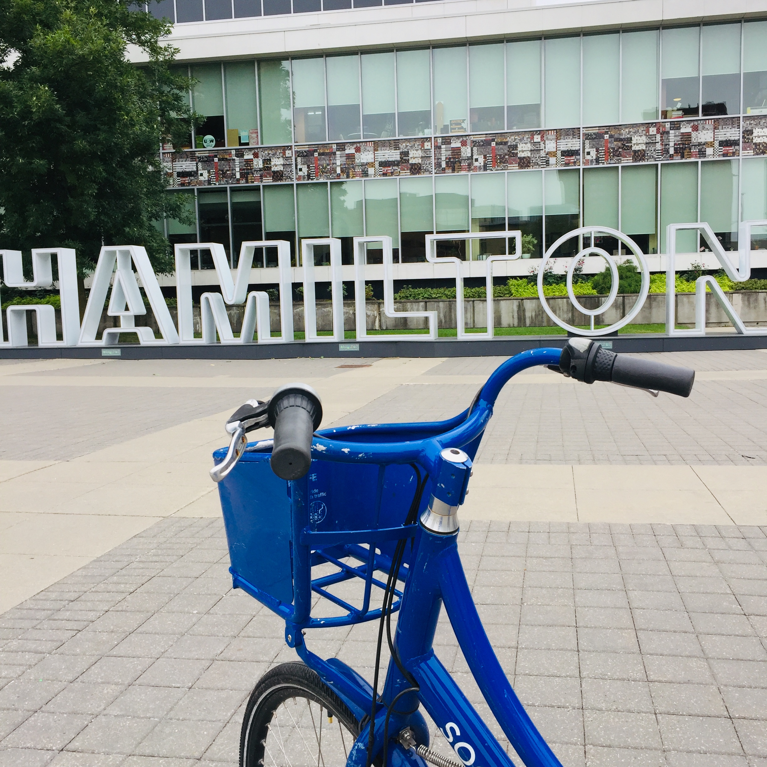 The handlebars and basket of a blue bike share bicycle captured from behind, with the Hamilton sign in the background