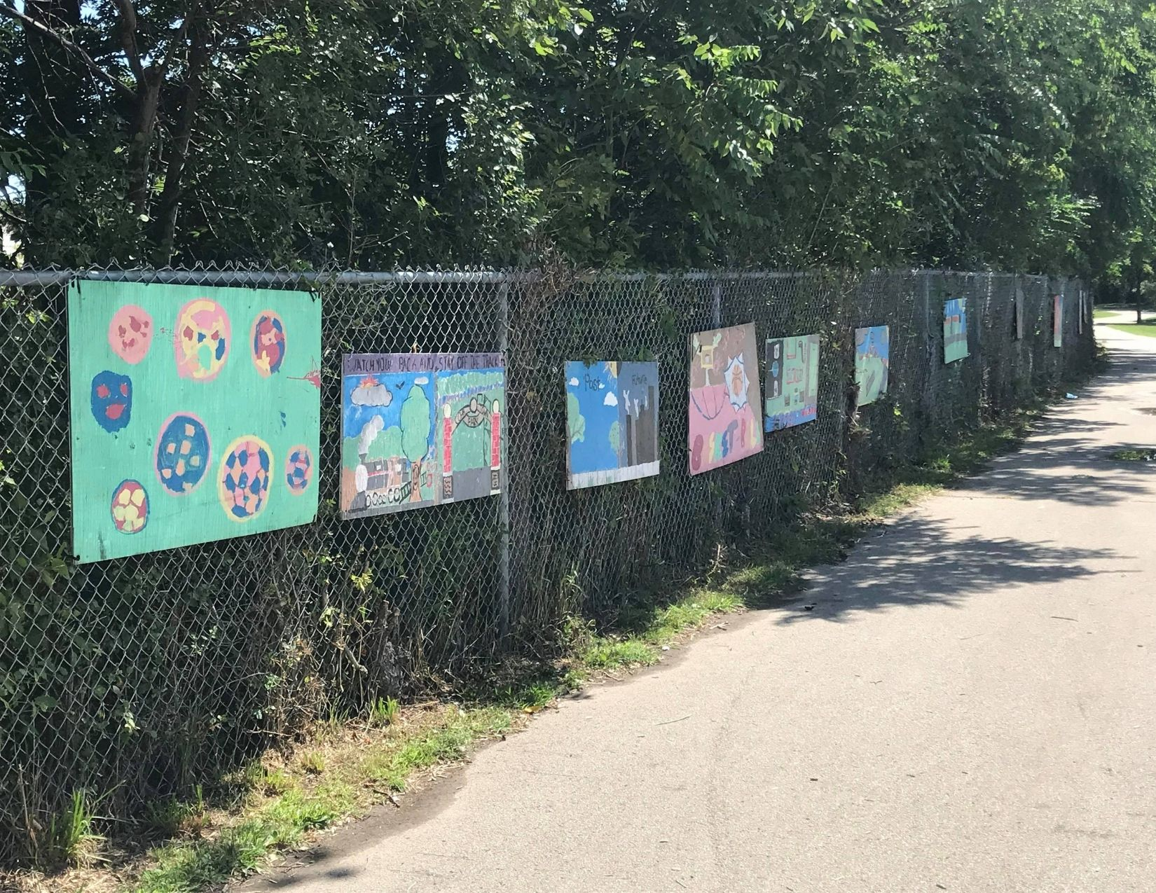 Children's art hanging on a fence beside a multi-use path