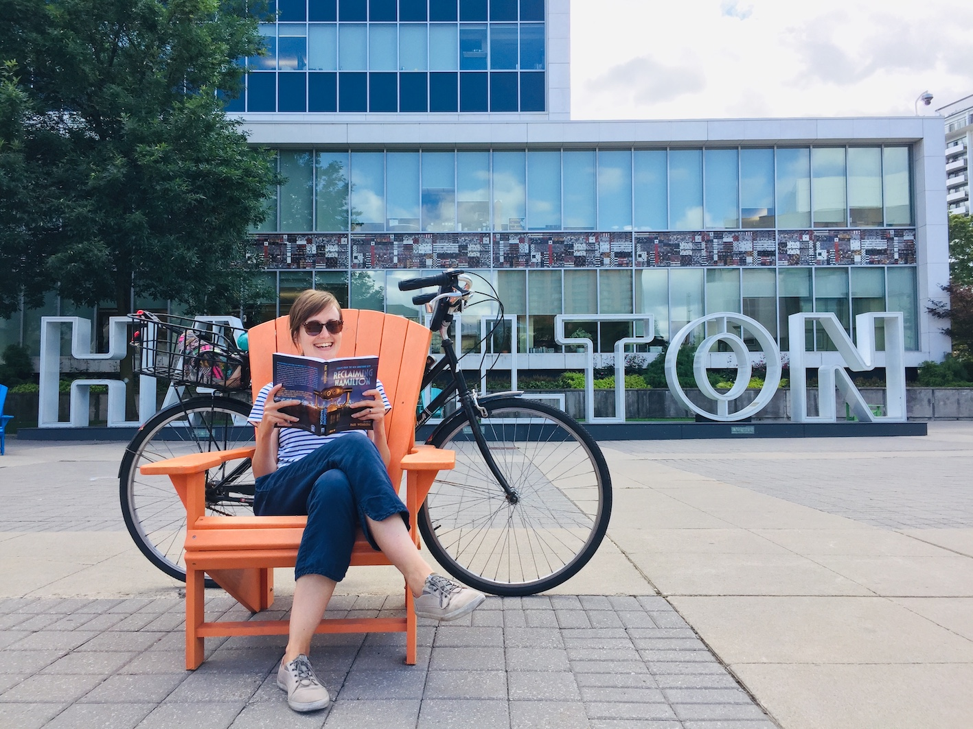 Jamie sitting in a Muskoka chair reading the Reclaiming Hamilton book. Her bike and the Hamilton sign are behind her
